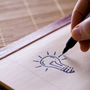 Man's hand drawing light bulb on notebook binder.